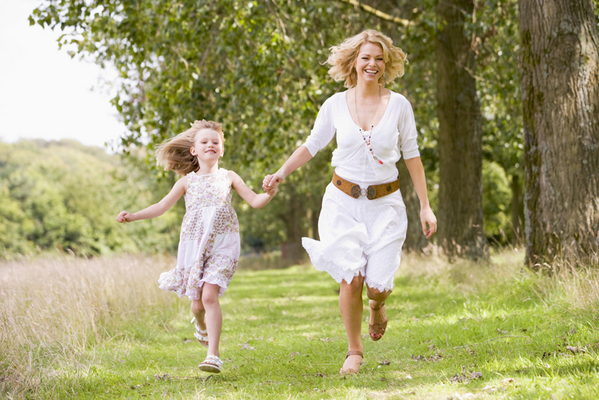 Mother and daughter walking on path holding hands smiling