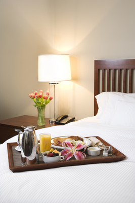 Breakfast tray laying on white bed in upscale hotel.