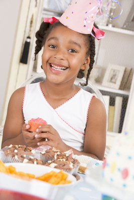 Young girl at party sitting at table with a cupcake smiling