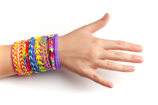 Child hand with colorful rubber rainbow loom bracelets isolated on white, trendy teenagers fashion accessories